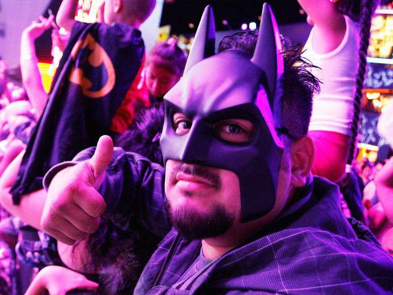 Anthony Vides wears a Batman mask while waiting for the midnight premiere of