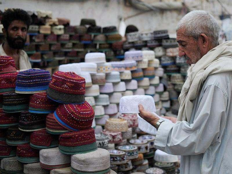 A Pakistani shopper selects a cap for the upcoming holy fasting month of Ramadan at a roadside shop in Karachi. (AFP Photo/Asif Hassan)