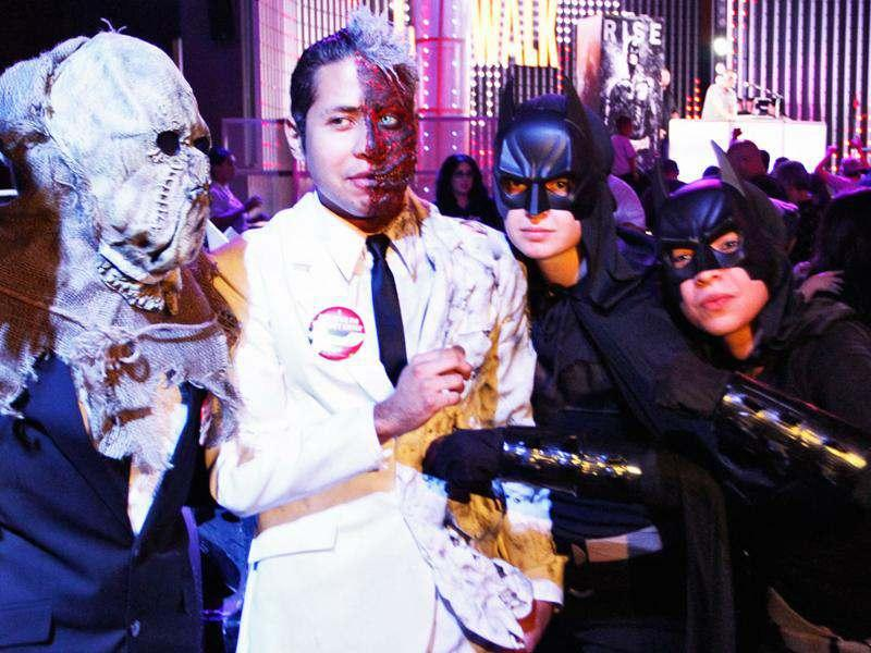 People, dressed as characters from Batman movies, pose while waiting for the midnight premiere of