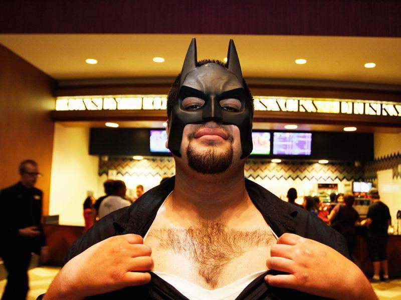 Jesus Alamo shows a Batman logo shaved into his chest hair, as he waits for the midnight premiere of