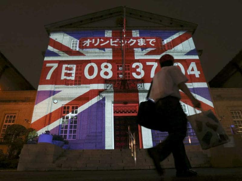 A man walks past a building, projecting a countdown clock to the opening of the London 2012 Olympic Games, at the British Embassy in Tokyo July 20, 2012. The lighting up with the Unicon flag together with the numbers of days, hours, minutes and seconds to go until the opening of the Olympic Games was projected on the front exterior of the Embassy's main building on Friday. The countdown will go until the actual time of the opening ceremony of the London 2012 Olympic Games.  Reuters/Kim Kyung-Hoon