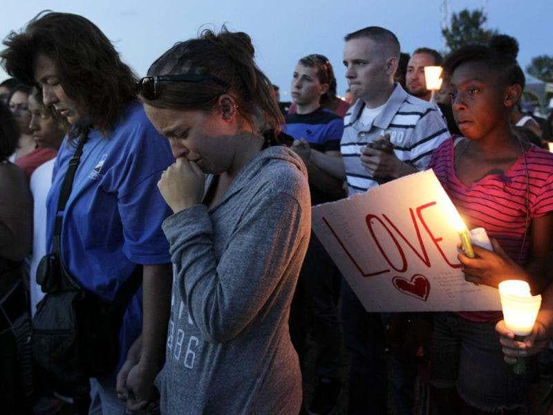 People attending a candle-light prayer gathering cry as they prayin Aurora, Colorado, across the street from the movie theater at the premiere of the new Batman movie where a gunman killed at least 12 people and wounded dozens of others in one of the deadliest mass shootings in recent US history. (AP Photo/Ted S. Warren)