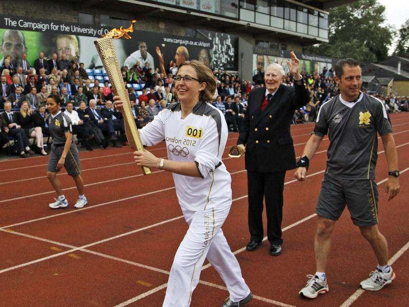 Oxford University doctoral student Nicola Byrom carries the Olympic Flame after it was passed from Sir Roger Bannister, 2nd right waving, on the running track at Iffley Road Stadium in Oxford, England. Bannister was the first person ever to run a sub four-minute-mileat this track in Oxford. (AP Photo)
