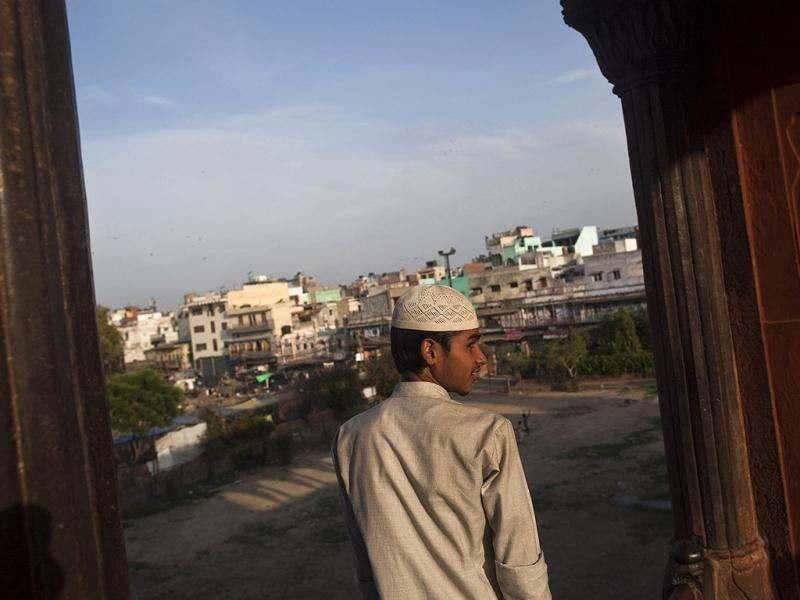 A Muslim boy looks at the residential complex through the Jama Masjid (Grand Mosque) before having his Iftar (fast-breaking) meal during the holy month of Ramadan in the old quarters of Delhi. (Reuters)