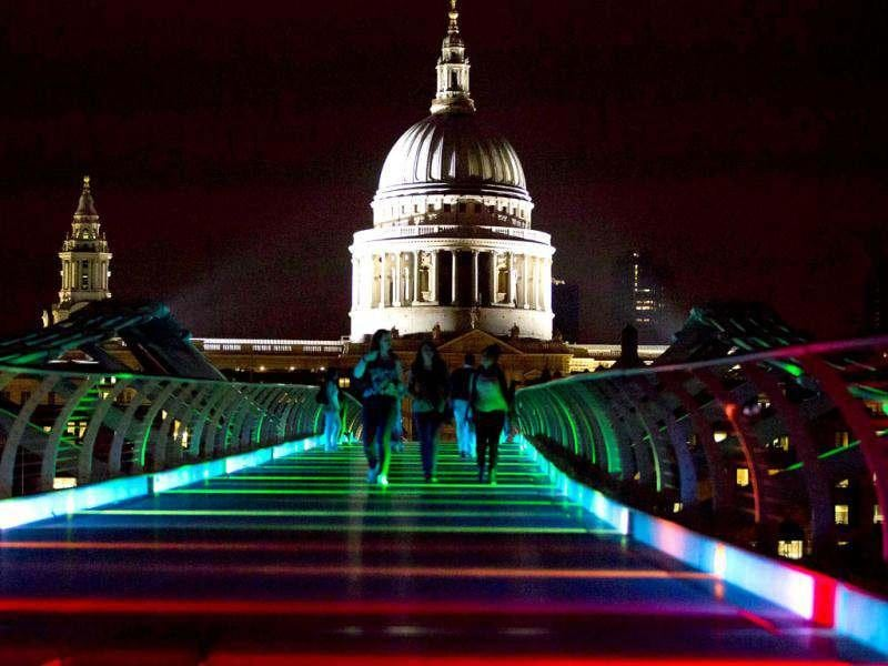 People walk on Millenium Bridge as it is lit up to celebrate the Olympics in London. St. Paul Cathedral is seen in the background. (Reuters Photo/Neil Hall)