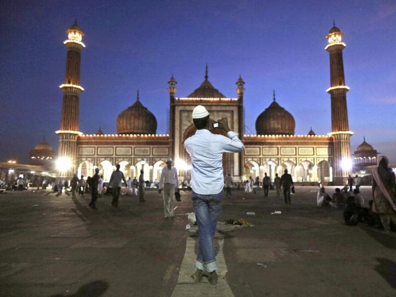 In this picture an Indian Muslim man takes a picture on the first night of the holy fasting month of Ramadan at Jama Masjid, in New Delhi, India. Muslims throughout the world are marking the month of Ramadan, the holiest month in Islamic calendar. (AP Photo/Kevin Frayer)