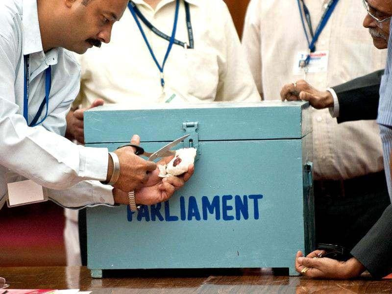 Election observers and officials open the seal of a ballot box as they begin tallying the Presidential election results, at the Parliament in New Delhi. AFP/Prakash Singh