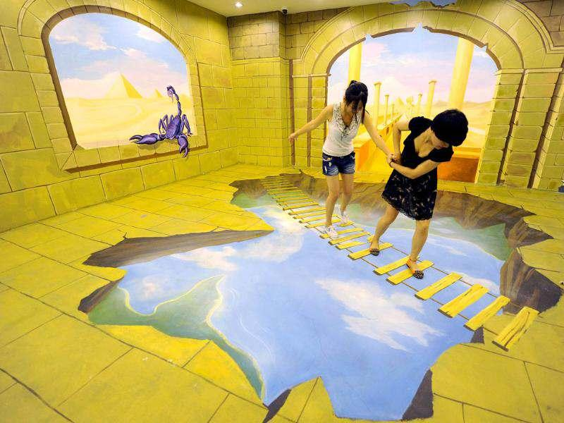 This picture shows visitors interacting with a 3D painting at the Magic Art Special Exhibition in Hefei, east China's Anhui province. (AFP photo).