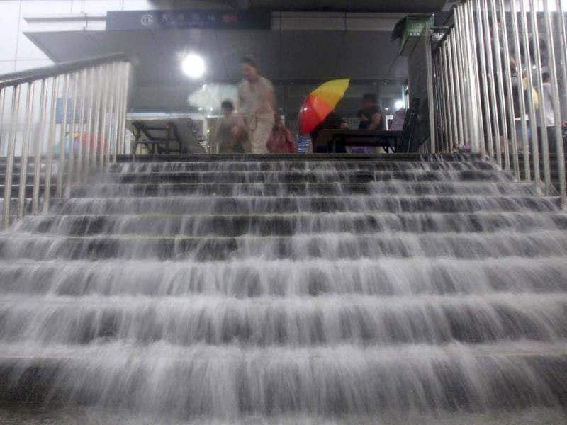 Flood water falls down a stairway as residents get out of the entrance to a subway station amid heavy rainfalls in Beijing. (Reuters/Stringer)