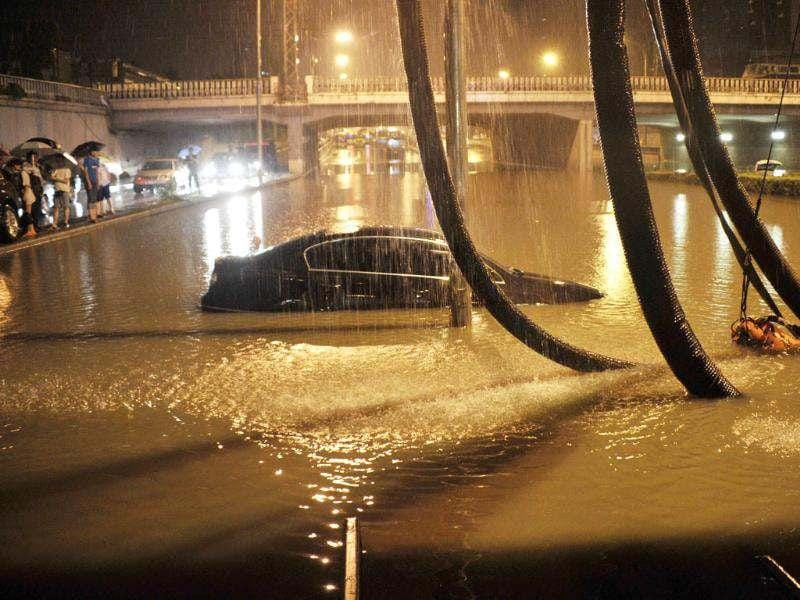 Residents look at a stranded car on a flooded street amid heavy rainfalls in Beijing. (Reuters/Stringer)