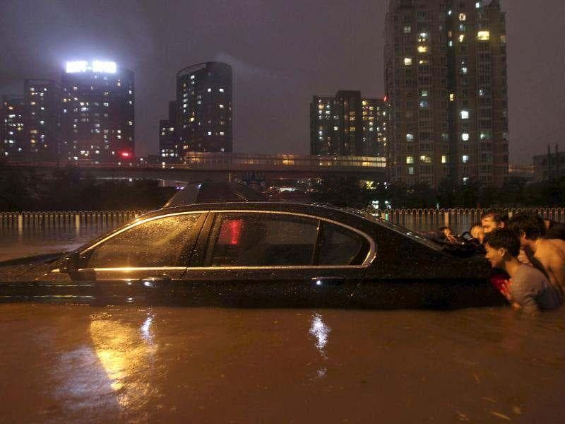 Residents push a stranded car on a flooded street amid heavy rainfalls in Beijing. (Reuters/Stringer)