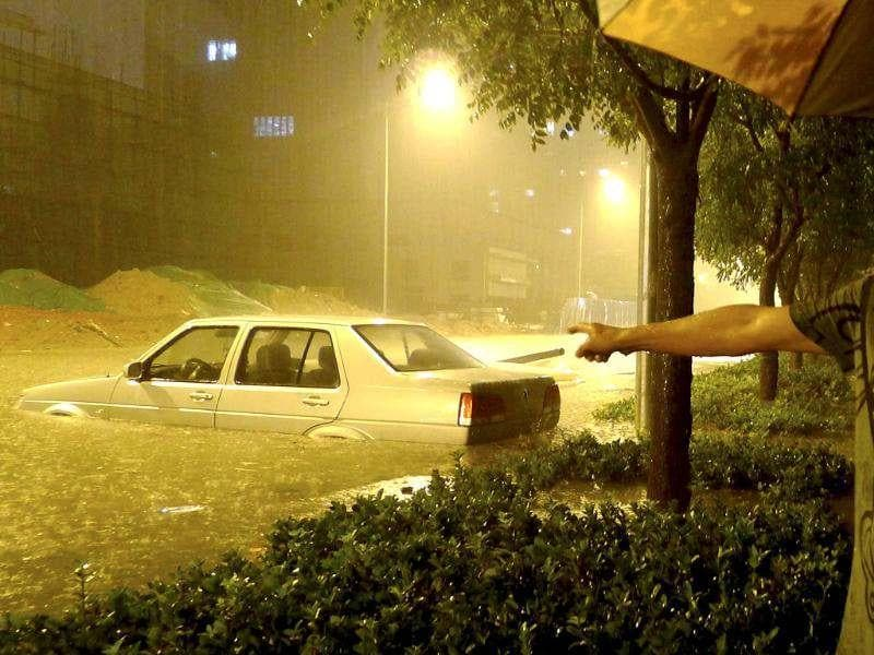 A driver points to his car which has been stranded for half an hour on a flooded street amid heavy rainfalls in Beijing. (Reuters/Stringer)