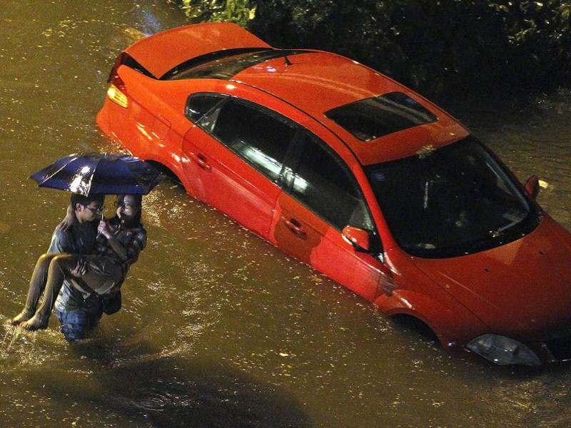 A Chinese man carries a woman past a car partially submerged in floodwaters following a heavy rain in Beijing. (AP Photo)