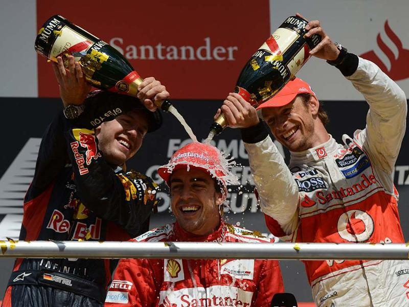 Red Bull Racing's German driver Sebastian Vettel (L), Ferrari's Spanish driver Fernando Alonso (C) and McLaren Mercedes' British driver Jenson Button (R) celebrate with champagne on the podium at the Hockenheimring circuit on July 22, 2012 in Hockenheim during the German Formula OneGrand Prix. AFP/ Dimitar Dilkoff