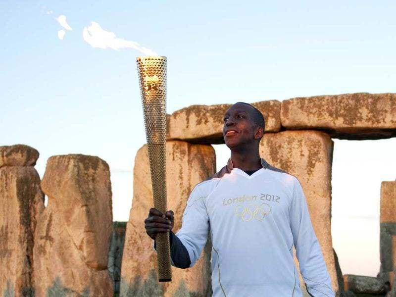 Former US Olympic athlete Michael Johnson holds the Olympic Torch at Stonehenge, a World Heritage site, in Salisbury, southern England. Come what may, Johnson will forever have Atlanta and those 10 days when he became the only male athlete ever to win both the 200 metres and 400 metres at the same Olympics. Reuters/Kieran Doherty