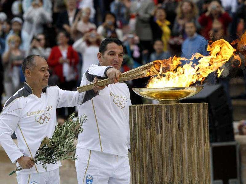 Greek veteran weighlifter Piros Dimas (R) and Chinese gymnast Li Ning light a cauldron with the Olympic Flame in Athens. Gymnast Li Ning won top honours in floor exercise, pommel horse and rings; he won silver on the vault and was part of the team that won silver in men's all-around event. Reuters/John Kolesidis