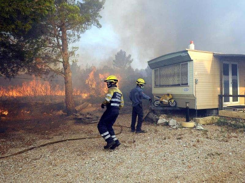 Firemen arrive to fight fire next to a mobilhome in Avinyonet de Puigventos village, near Figueras. Fire had been brought under control in some areas on the morning, but the main roads in the area, the A9 motorway and the D900, remain closed after a wildfire whipped up by strong winds in northeast Spain has left three people dead and more than 20 injured, trapping thousands of residents indoors. AFP/Remy Gabalda