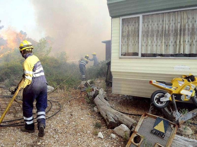 Firemen try to extinguish fire next to a mobilhome in Avinyonet de Puigventos village, near Figueras. AFP/Remy Gabalda