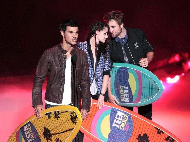 Actor Taylor Lautner speaks, as actors Kristen Stewart and Robert Pattinson watch, as they accept the Ultimate Choice Award at the 2012 Teen Choice Awards. (Reuters photo)