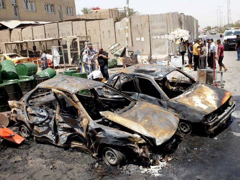People inspect the aftermath of a car bomb attack in Baghdad's Shiite enclave of Sadr City, Iraq. An onslaught of bombings and shootings killed scores of people across Iraq in the nation's deadliest day so far this year. AP poto/Karim Kadim