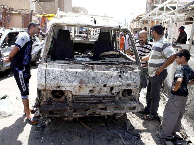 People inspect a destroyed vehicle after a bomb attack in Madain, about 15 miles (25 kilometers) southeast of Baghdad, Iraq. AP photo/Karim Kadim