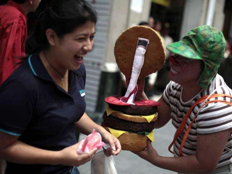 A clown shows a picture of the leg of a woman in a hamburger during the inauguration parade of the 4th Latin America Clown Congress in Guatemala City. Two hundred clowns from Latin America participated during the congress. Reuters/Jorge Dan Lopez
