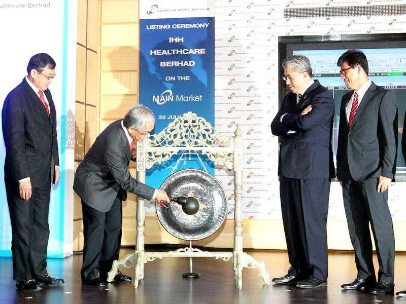 Chairman of IHH Healthcare Abu Bakar Suleiman hits a gong to mark the company's listing debut at Malaysia Stock Exchange in Kuala Lumpur. AFP