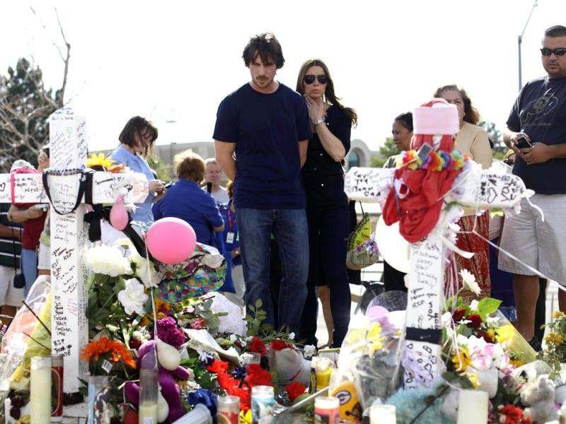 Actor Christian Bale and his wife Sibi Blazic look at the memorial to the victims of Friday's mass shooting, Tuesday, July 24, 2012, in Aurora, Colo. Twelve people were killed when a gunman opened fire during a late-night showing of the movie The Dark Knight Rises, which stars Bale as Batman.