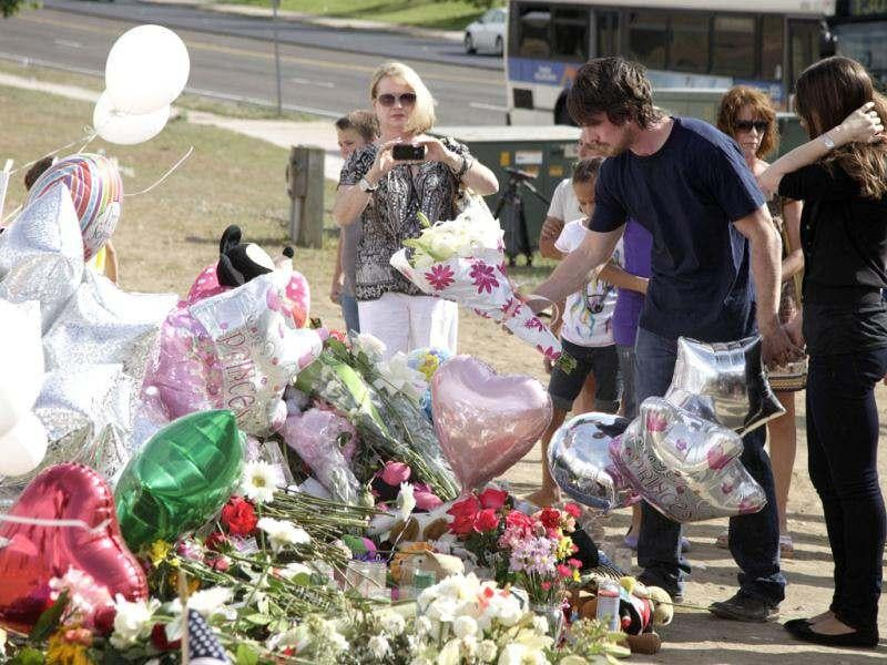 Actor Christian Bale and his wife Sibi Blazic place flowers on the memorial to the victims of Friday's mass shooting, Tuesday, July 24, 2012, in Aurora, Colorado. Twelve people were killed when a gunman opened fire during a late-night showing of the movie The Dark Knight Rises