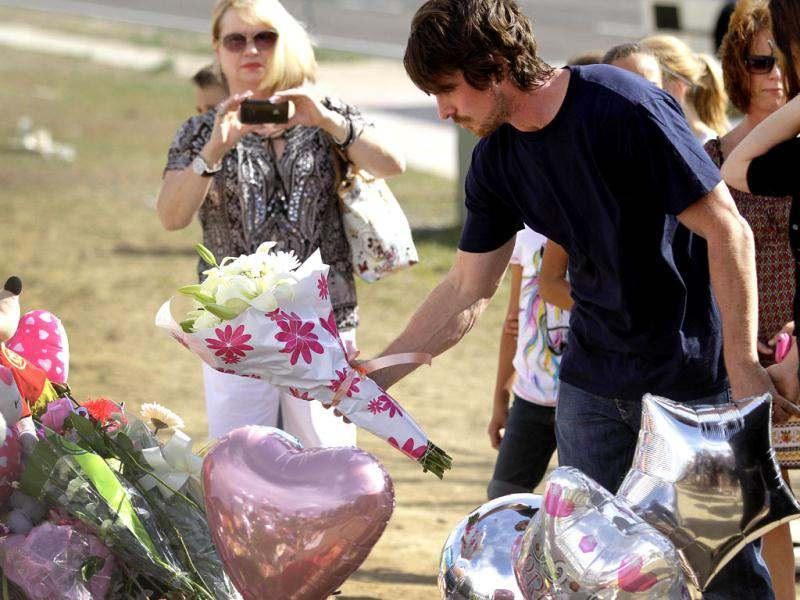 Actor Christian Bale place flowers on the memorial to the victims of Friday's mass shooting in Aurora, Colorado.