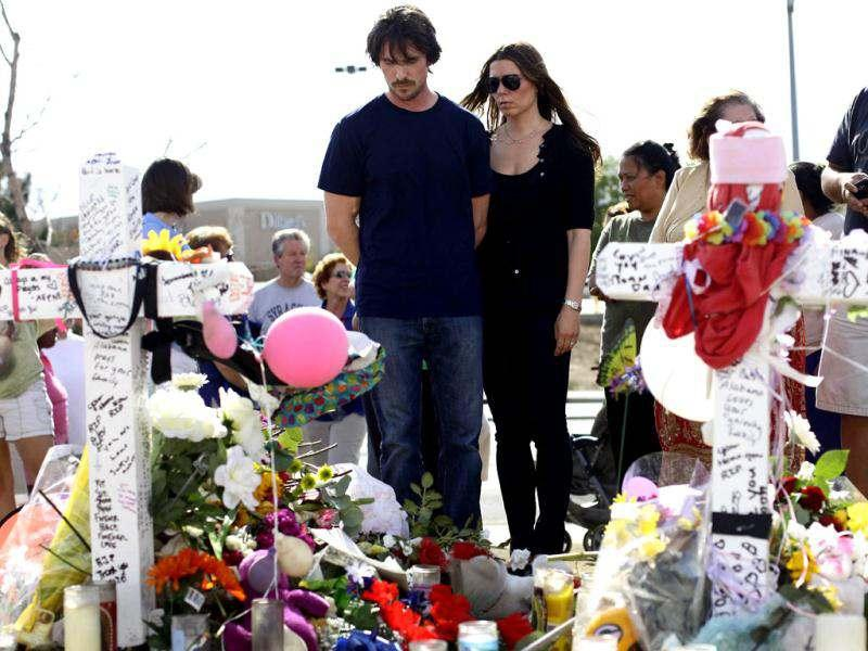 Actor Christian Bale and his wife Sandra Blazic sadly look at the flowers and cards at the memorial across the street from the Century 16 movie theater.