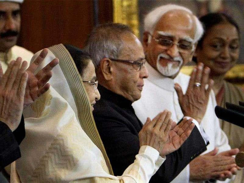 President Pranab Mukherjee gestures after taking oath as 13th President of India as his predecessor Pratibha Patil, vice president Hamid Ansari and Lok Sabha speaker Meira Kumar applaud at a special ceremony in the Central Hall of Parliament in New Delhi. PTI/Shahbaz Khan