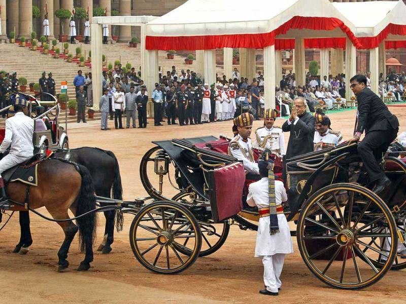 New President Pranab Mukherjee, in a traditional horse driven carriage, gestures as he arrives at the Presidential Palace, in New Delhi. AP/Manish Swarup