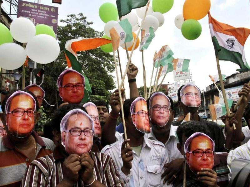 Supporters of Congress party wear face masks of Pranab Mukherjee as they celebrate his coronation as President of India, in Kolkata. AP/Bikas Das