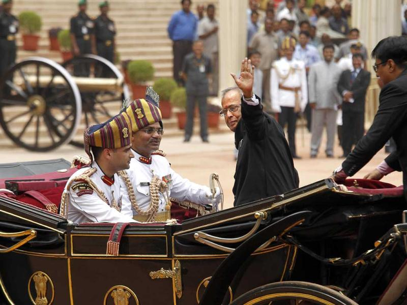New President Pranab Mukherjee, in a traditional horse driven carriage, waves to the media as he arrives at the Presidential Palace, in New Delhi. AP/Manish Swarup