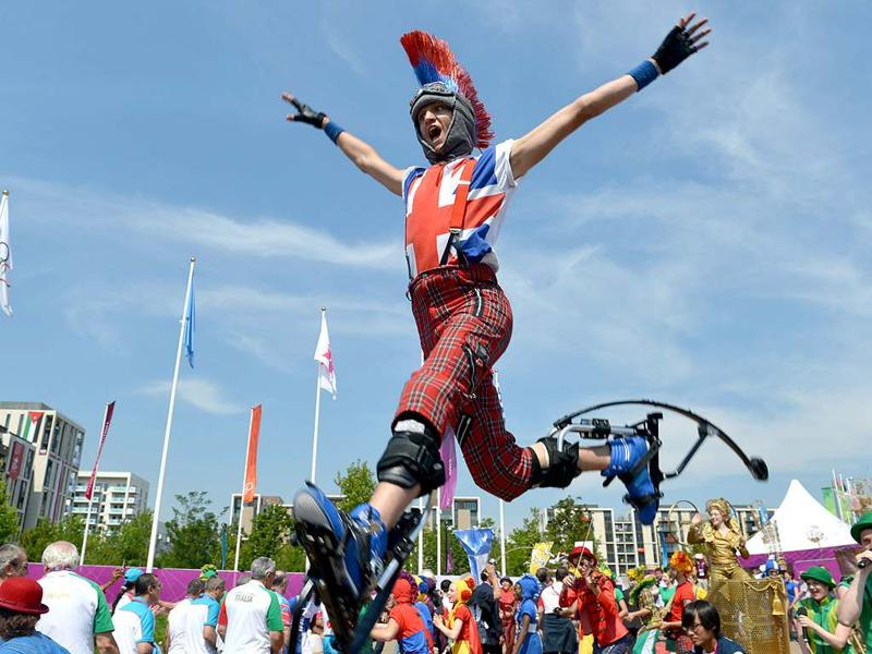 An artist performs on jumping stilts during an arrival ceremony for athletes at the Olympic Village in London, two days before the start of the London 2012 Olympic Games. AFP/Adek Berry