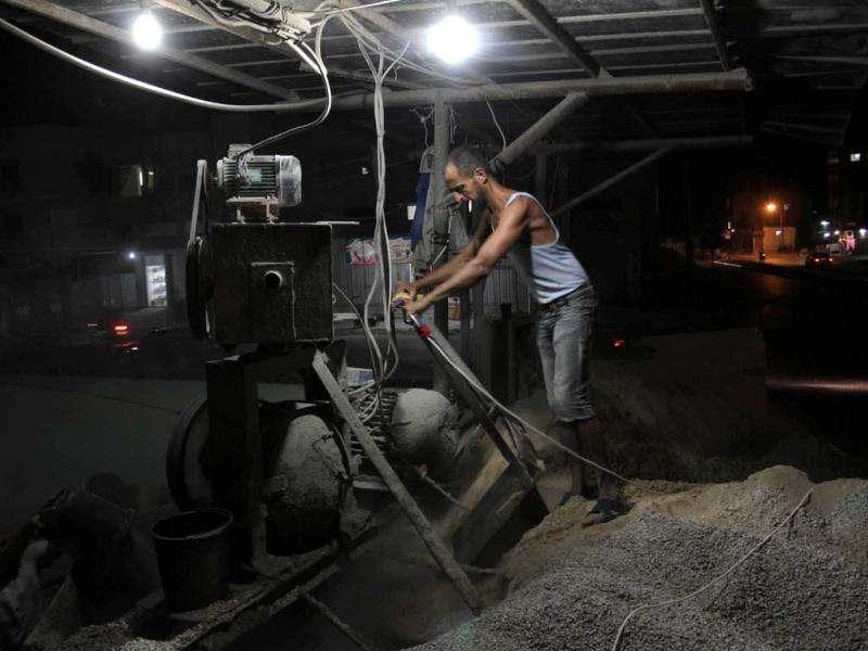 Palestinian workers recycle cement at a factory work at night in the month of Ramadan Rafah town in the southern Gaza Strip. AFP/Said Khatib