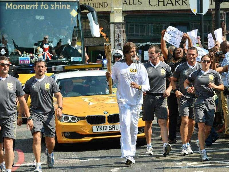 Amitabh Bachchan (C) carries the Olympic flame in London on July 26, 2012, one day before the start of the London 2012 Olympic Games. (AFP)
