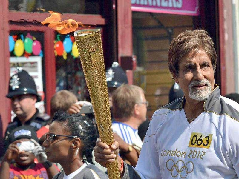 Bollywood actor Amitabh Bachchan carries the Olympic Flame in London on July 26, 2012, one day before the start of the London 2012 Olympic Games. (AFP)