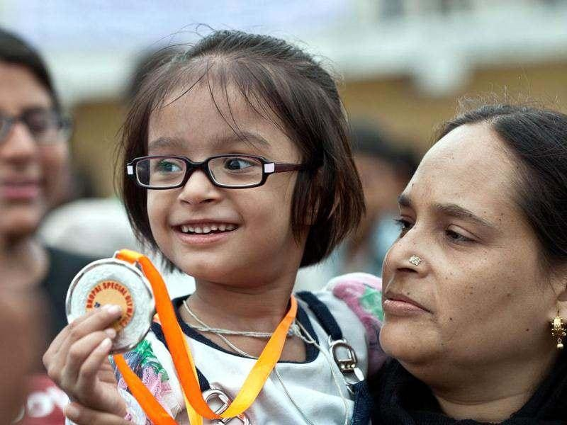 Zehra, a five year old disabled child suffering the effects of the 1984 Bhopal disaster, shows her gold medal she won in crab walking event during a Special Olympics in Bhopal. AFP photo/Prakash Singh