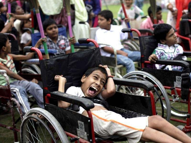 Children suffering with birth defects wait to compete in a wheel chair race during a Special Olympics held by the survivors of the deadly 1984 Bhopal gas leak in an effort to shame Olympic sponsor Dow Chemical Co. on the eve of the London Games in Bhopal. AP photo/Altaf Qadri