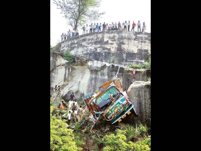 Police officers inspect the wreckage of a truck after it veered off a mountain road and plunged into a gorge about 65 kilometers southwest from Jammu. AP/Channi Anand