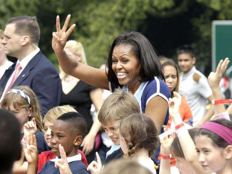 US first lady Michelle Obama poses for photos with schoolchildren during a 'Let's Move!' event for about 1,000 American military children and American and British students at the US ambassador's residence in London, ahead of the 2012 Summer Olympics. (AP Photo/Lefteris Pitarakis)