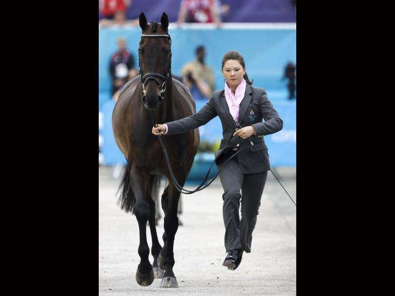 Thailand's Nina Ligon runs with her horse Butts Leon during horse inspection for the equestrian eventing competition at Greenwich Park, the site for the equestrian and modern pentathlon events at the 2012 Summer Olympics in London. (AP Photo/Markus Schreiber)