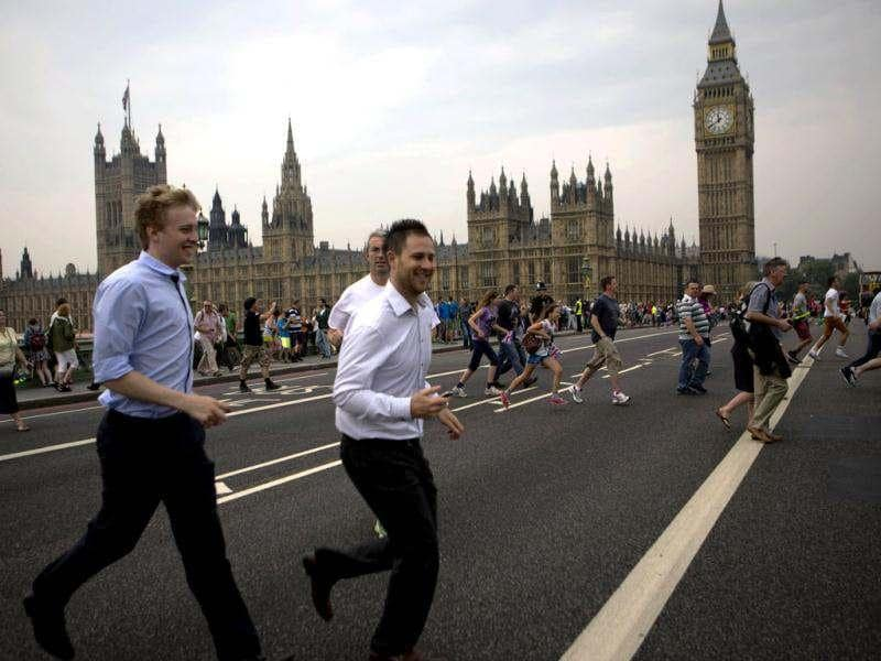 People cross the Westminster bridge to watch the royal barge Gloriana carry the Olympic flame along the river Thames, ahead of the 2012 Summer Olympics, on the final day of the Torch Relay, in London. (AP Photo/Emilio Morenatti)
