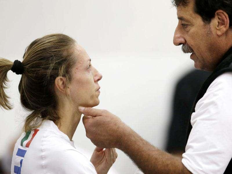 Italy's five times olympic gold medalist Valentina Vezzali, left, talks with her coach Giulio Tommasini during a fencing training session in the ExCel Centre, at the 2012 Summer Olympics in London. (AP Photo/Andrew Medichini)