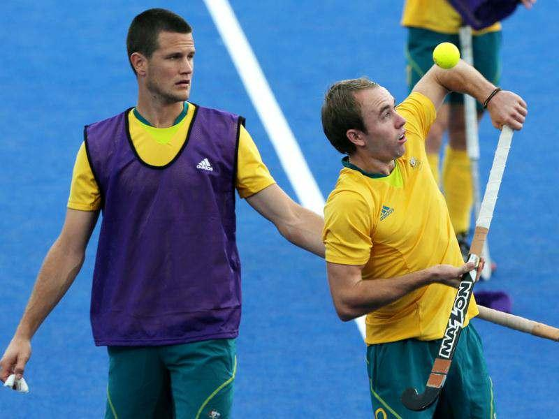 Australia's Matthew Swann, right, playfully balances a ball before the team's practice match against Germany at the 2012 Summer Olympics, in London. (AP Photo/Eranga Jayawardena)