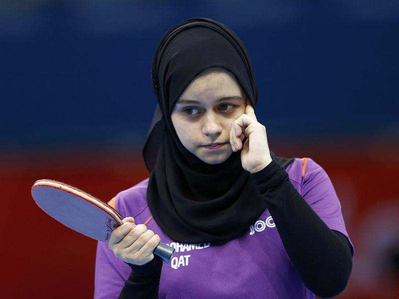 Qatar's Aia Mohamed adjusts her headscarf during her women's singles preliminary round table tennis match against Canada's Zhang Mo at the ExCel venue of the London 2012 Olympic Games in London. Reuters/Grigory Dukor