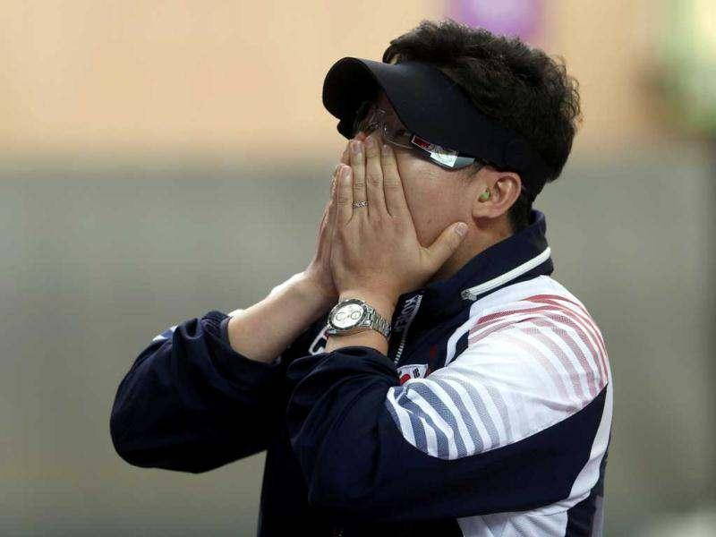 South Korea's Jin Jong-oh covers his face after winning the men's 10m air pistol final at the London 2012 Olympic Games in the Royal Artillery Barracks at Woolwich in London. Reuters/Eddie Keogh