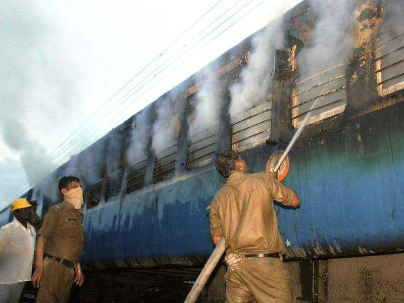 A fire fighter douses fire coming out from a coach of a passenger train at Nellor nearly 500 kilometers (310 miles) south of Hyderabad. AP Photo
